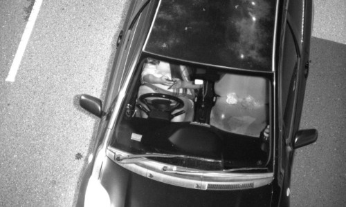 Photo captured by mobile phone detection camera, showing a driver using their phone while driving